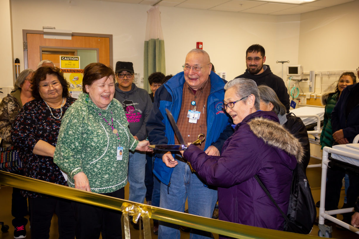 Group of people smiling and laughing inside Nome hospital as woman holds large scissors up to gold-colored ribbon.