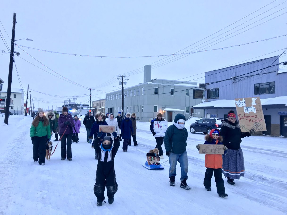 Group of marchers walks down Nome's Front Street on a snowy winter day.