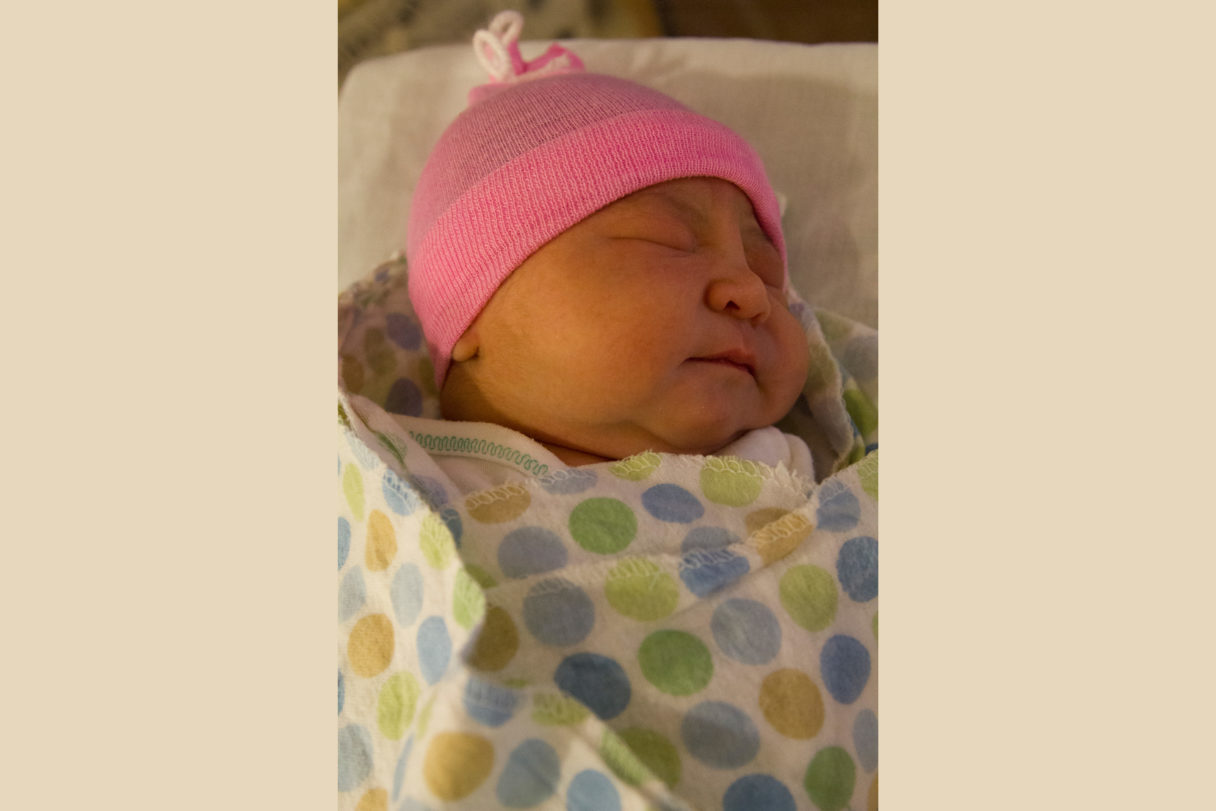 Image of newborn child in pink hat and polka-dotted blanket