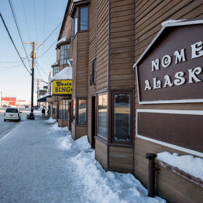 """Snowy sidewalk and large sign reading """"Nome Alaska"""" along a wood-paneled building on a winter's day in Nome."""