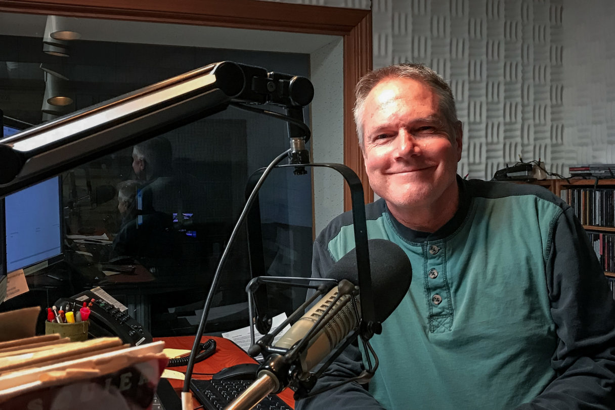 Man in green shirt stands behind radio microphone and sound board, smiling at camera.