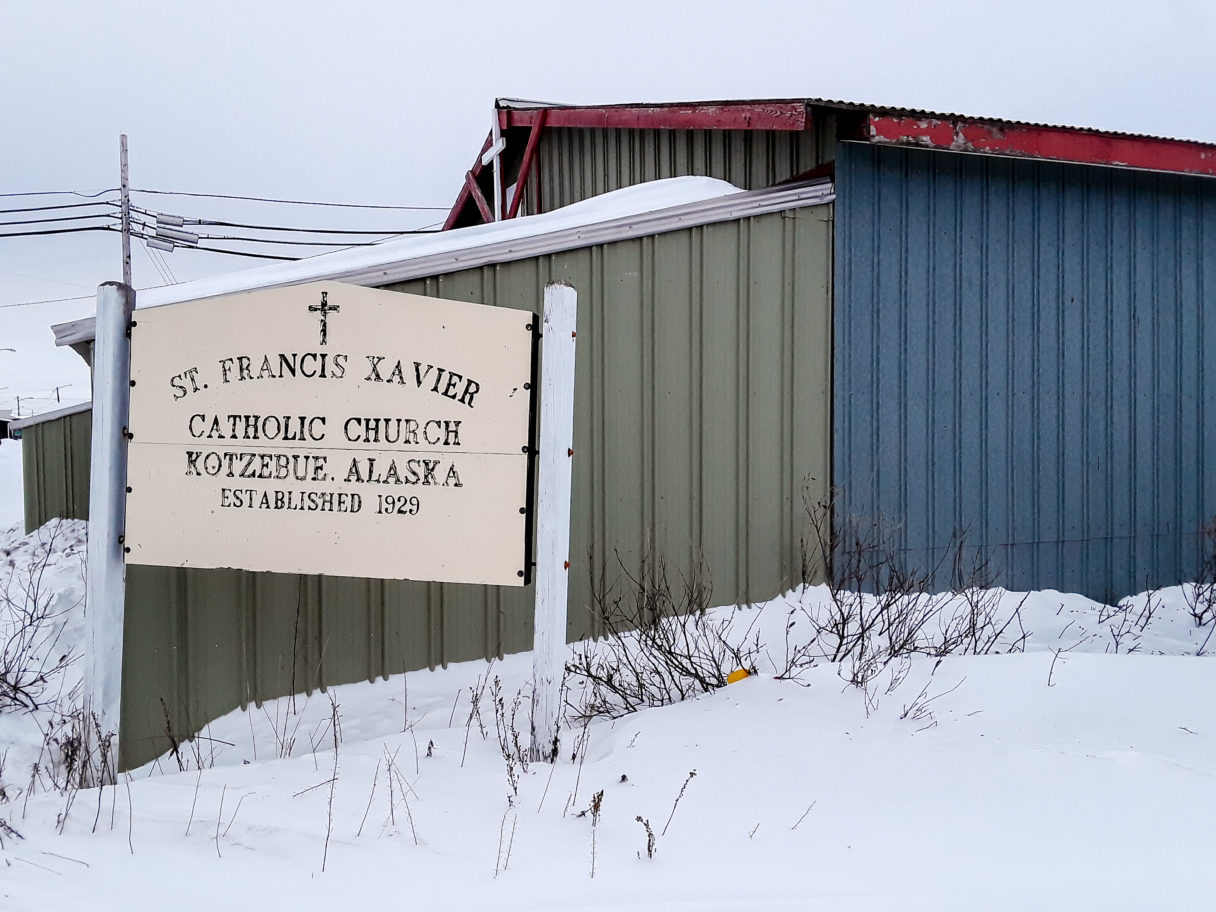 "Sign reading ""St. Francis Xavier Catholic Church, Kotzebue, Alaska, Established 1929"" standing in front of a building with green and blue metal siding. Snow covers the ground."