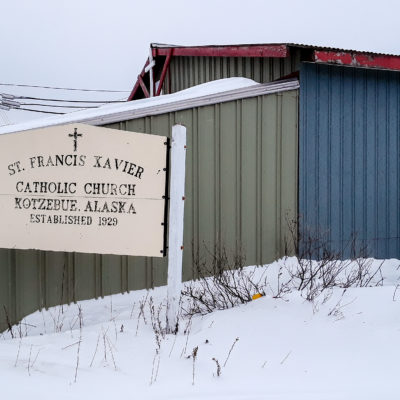 """Sign reading """"St. Francis Xavier Catholic Church, Kotzebue, Alaska, Established 1929"""" standing in front of a building with green and blue metal siding. Snow covers the ground."""