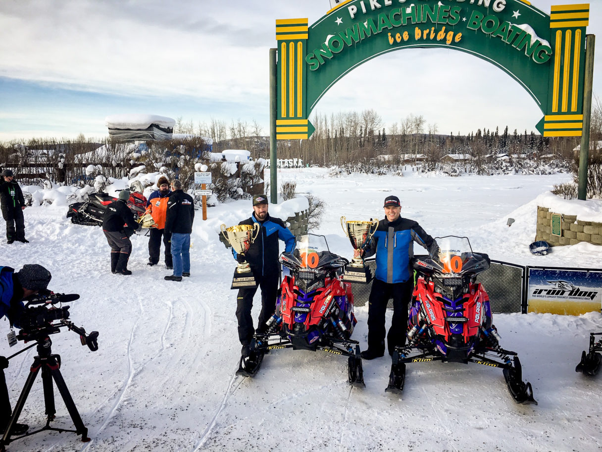 Two men in heavy winter gear stand next to snowmachines (snowmobiles) near a green-and-yellow arch that marks the finish line of the Iron Dog Snowmachine Race.