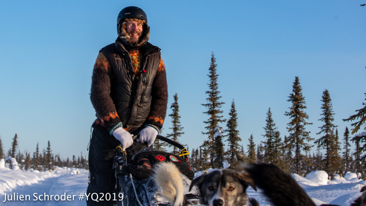 Smiling man wearing winter clothes stands atop a sled passing by, driven by sled dogs along a snowy forest trail.
