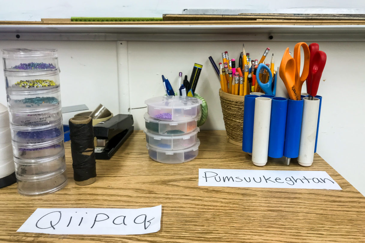 A wooden desk with various pens, pencils, scissors, and other office supplies, several of them labeled with Siberian Yupik words.