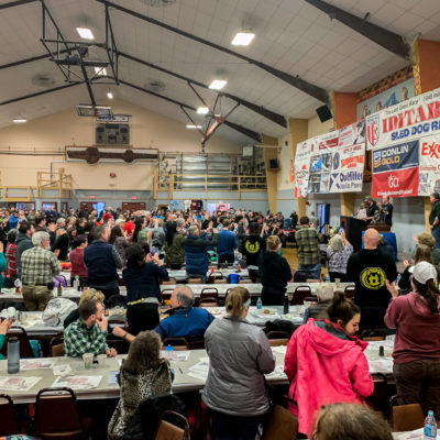 Iditarod fans stand and cheer Pete Kaiser in a large gymnasium, converted into a banquet hall.
