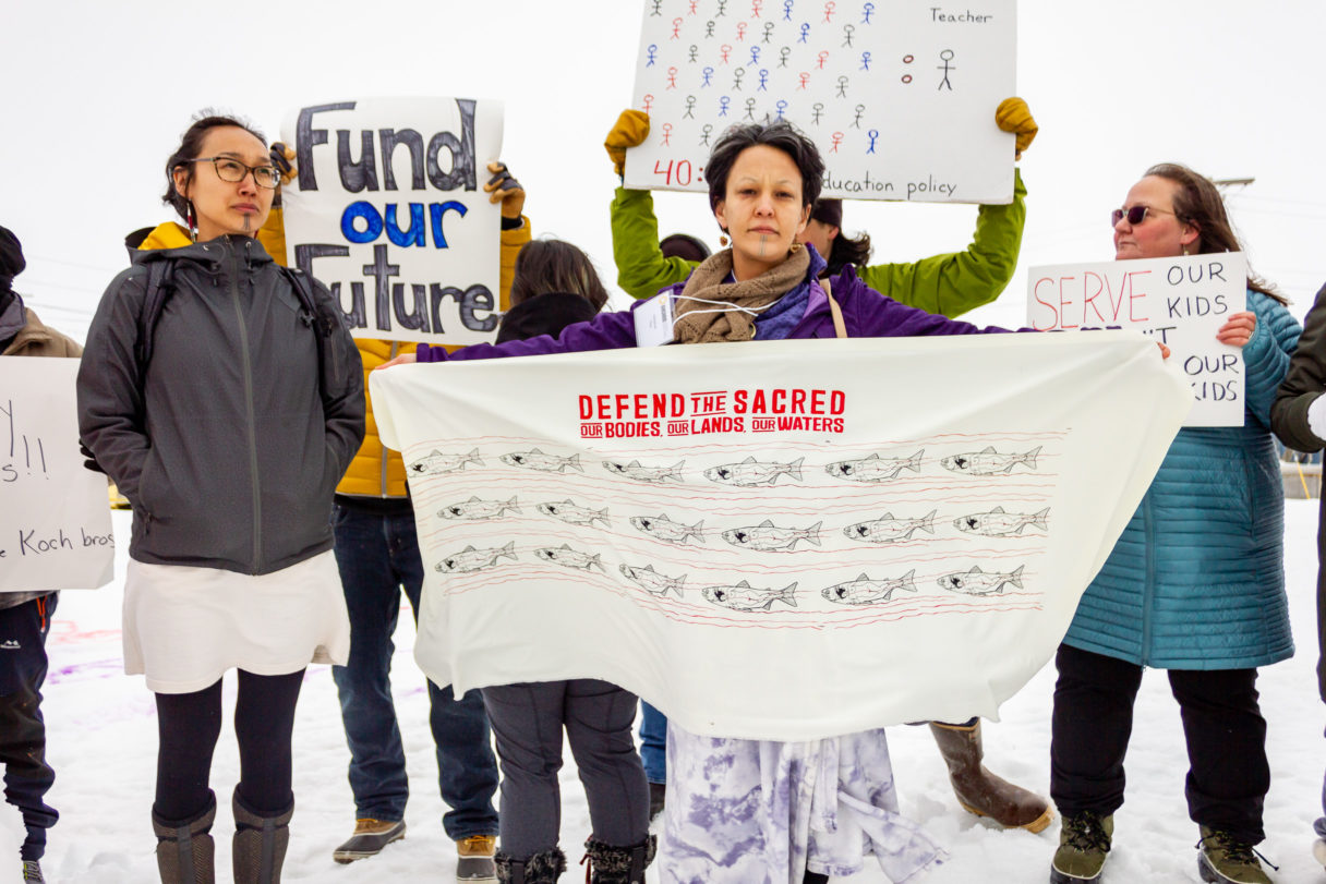 """People protesting outside Old St. Joe's meeting hall; one holds a large banner reading """"Defend the Sacred."""""""
