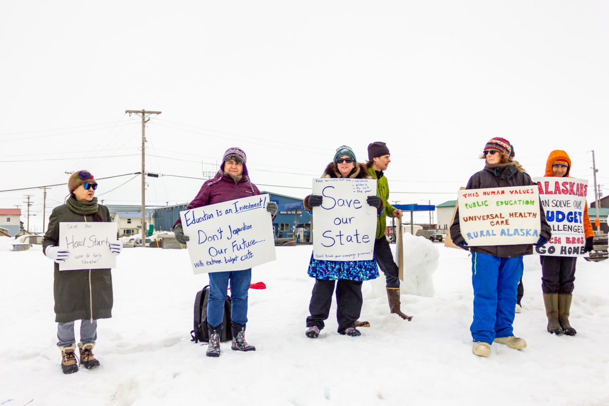 Protesters dressed in heavy winter gear stand outside Old St. Joe's in Nome