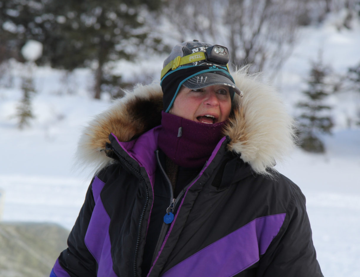 Woman in purple and black parka with large fur ruff