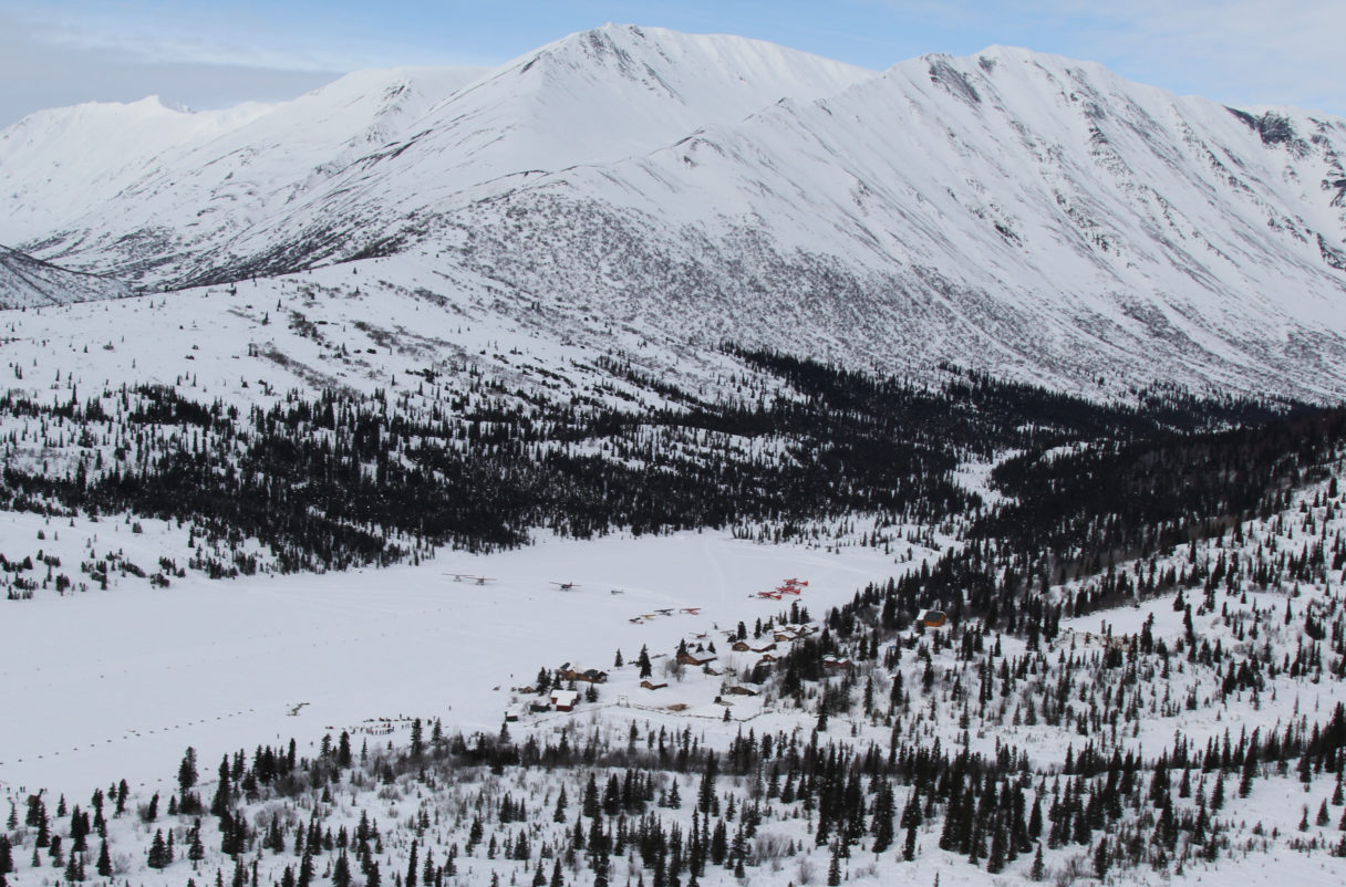 Aerial view of snow-covered mountains and Iditarod checkpoint in a valley, surrounded by forest