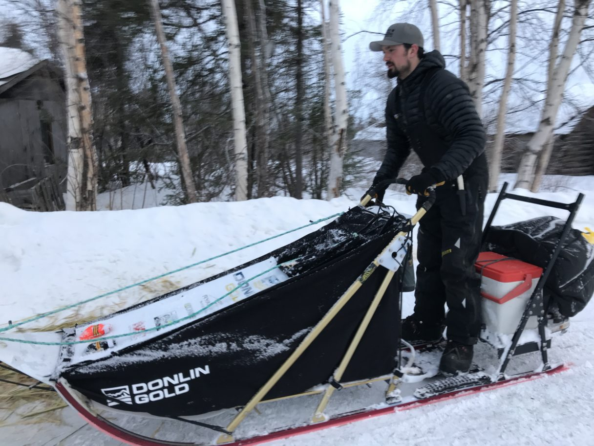 Man in black parka rides sled along a snowy trail