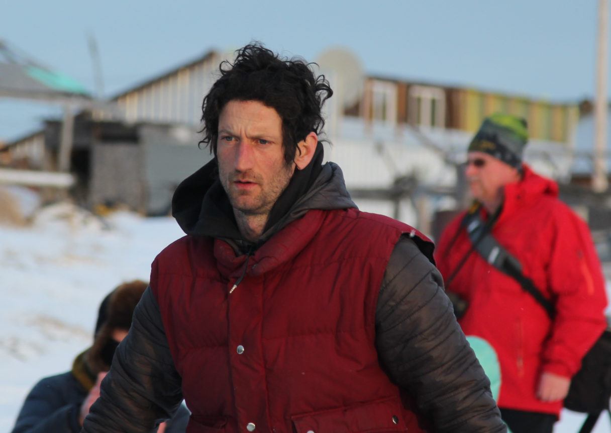 Profile of dark-haired musher wearing grey parka and red vest