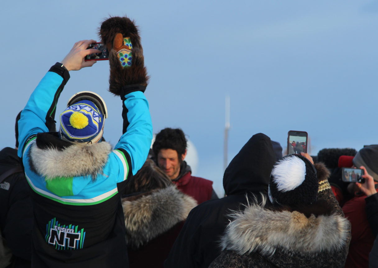 In foreground, spectators hold up smartphone cameras to Nicolas Petit, seen in background in a red vest, grey jacket and winter hat.