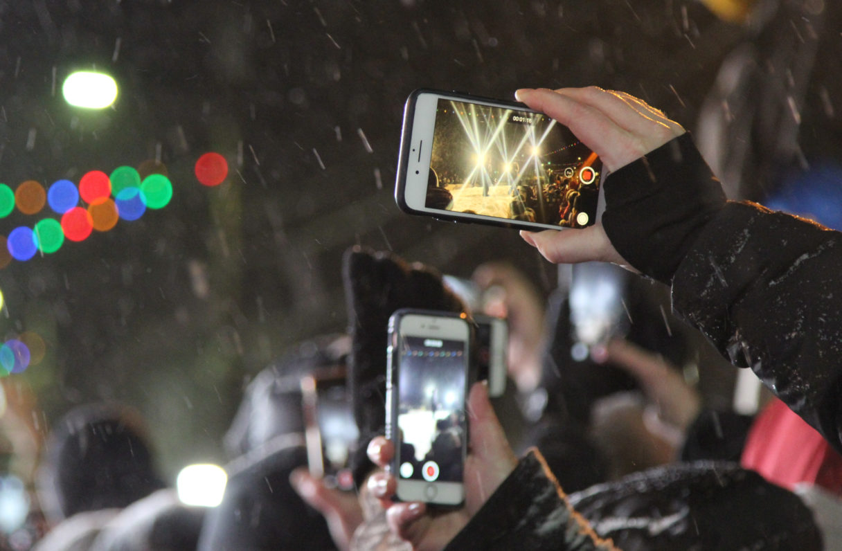 A focus on smartphone cameras held out in the direction of the Iditarod finish line chute against a snowy background and the lights of Front Street.