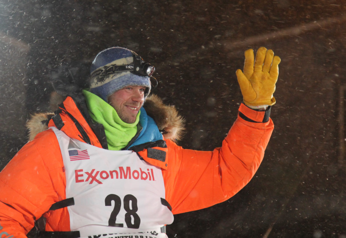 Musher in orange parka smiling while waving at race fans.