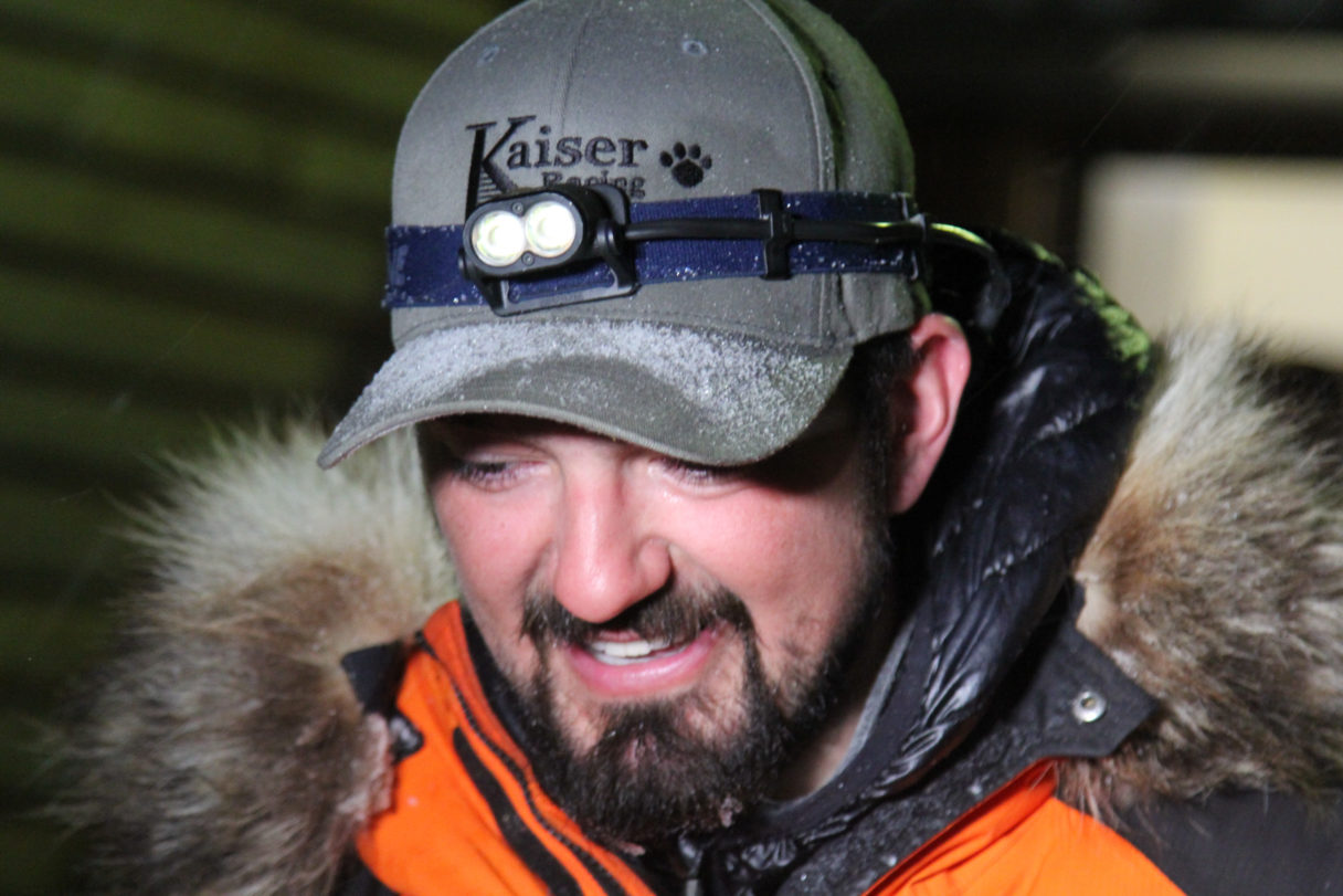 Close-up of Pete Kaiser, wearing grey hat, headlamp and orange-and-black parka