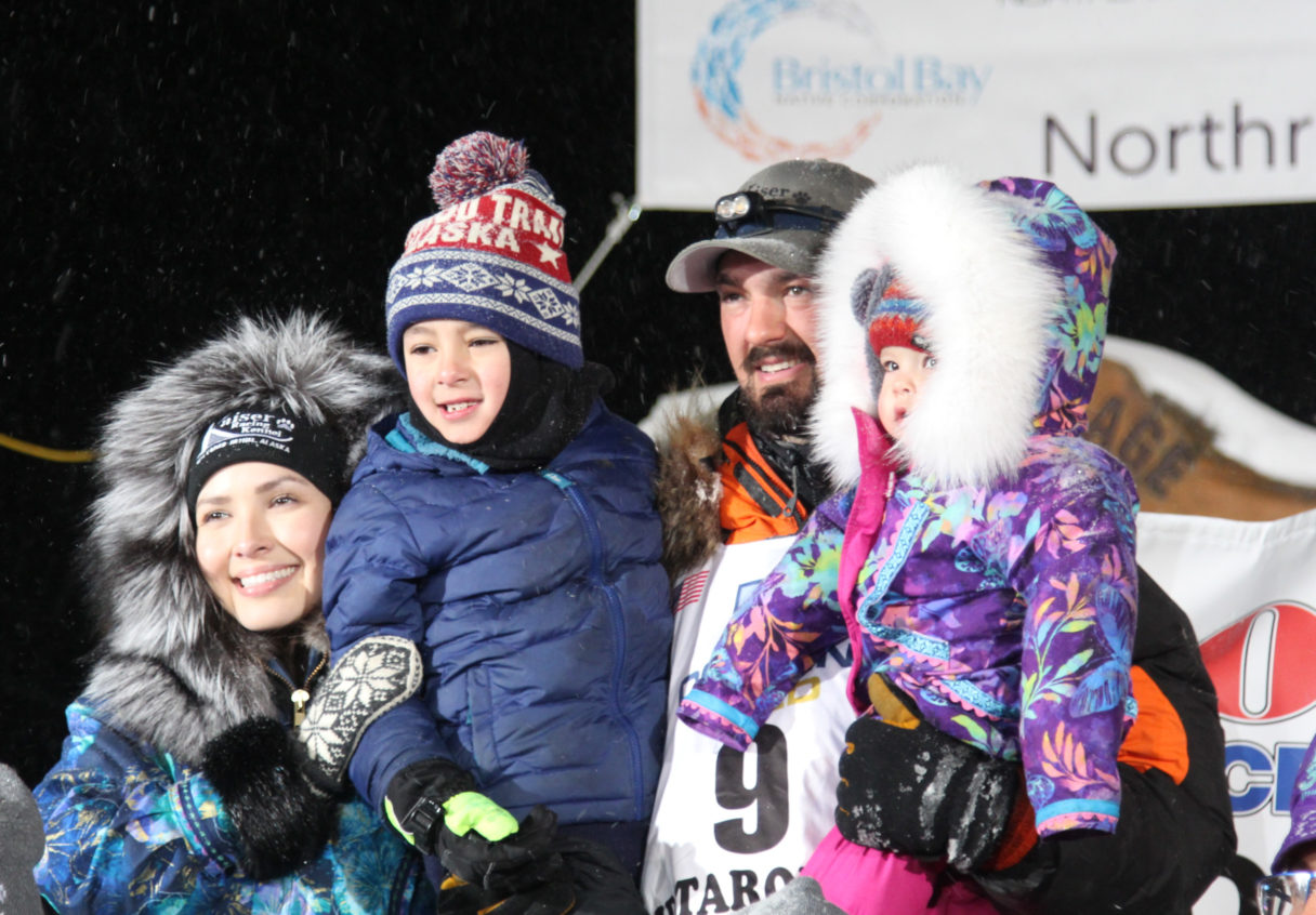 Family, all clad in heavy jackets, smile under the Iditarod finish line.