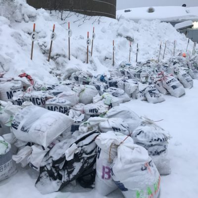 Snow-covered nylon bags, clustered together on the ground.