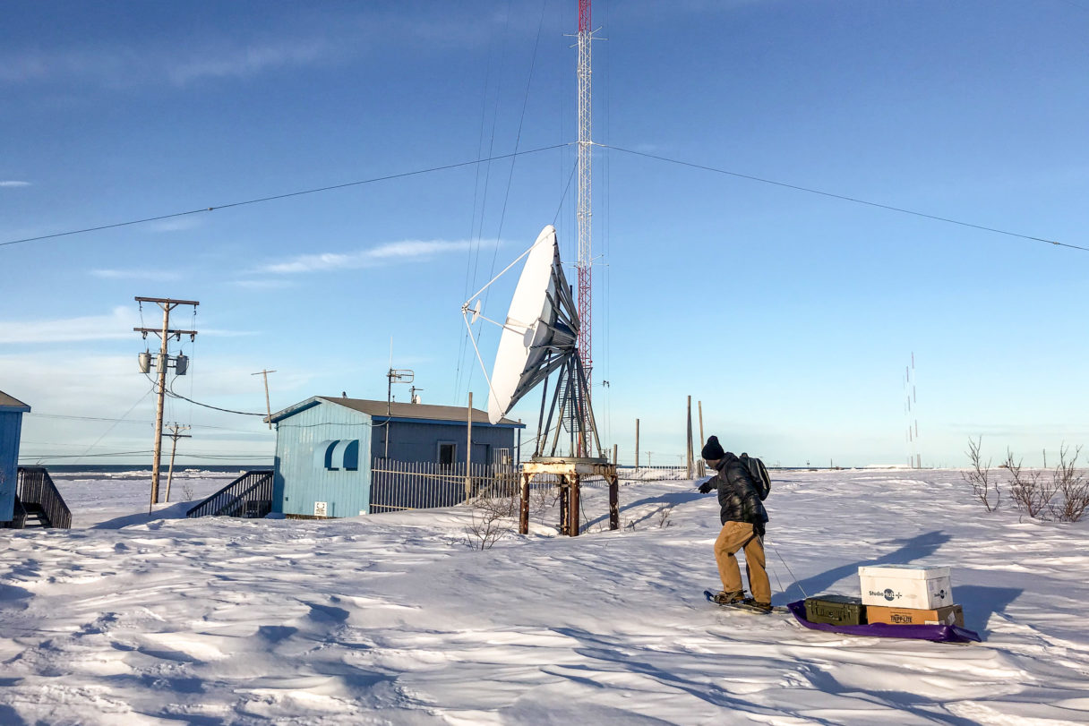 Man on snowshoes walks over snow drifts to remote AM transmitter tower site