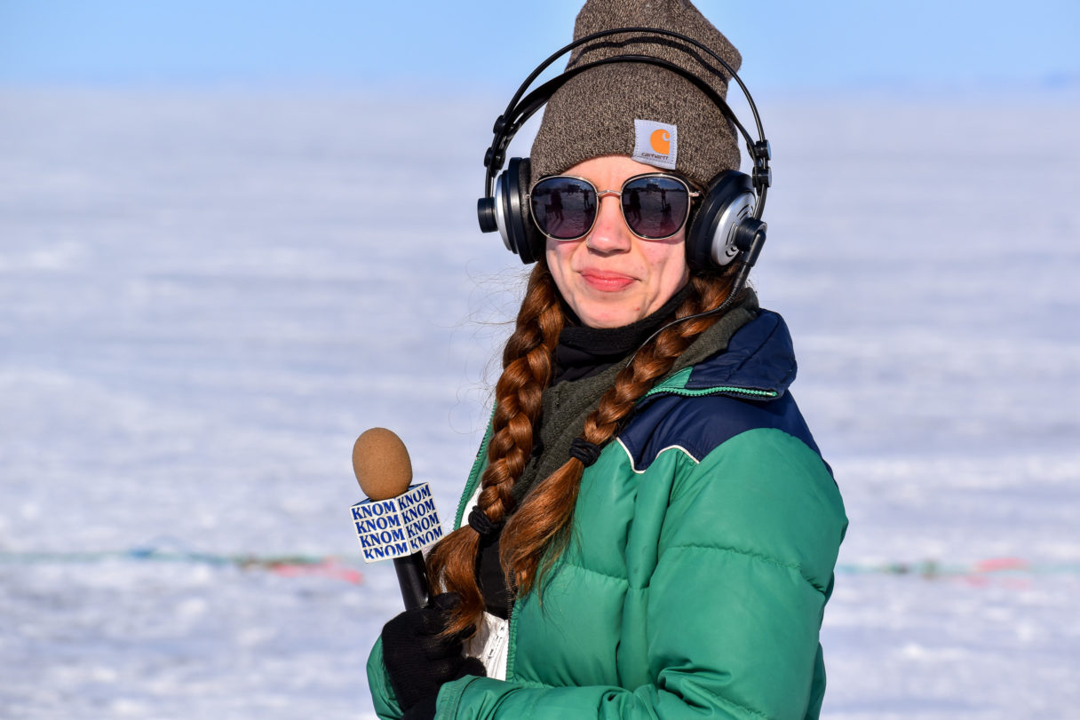"Woman in green parka holds microphone with ""KNOM"" logo"