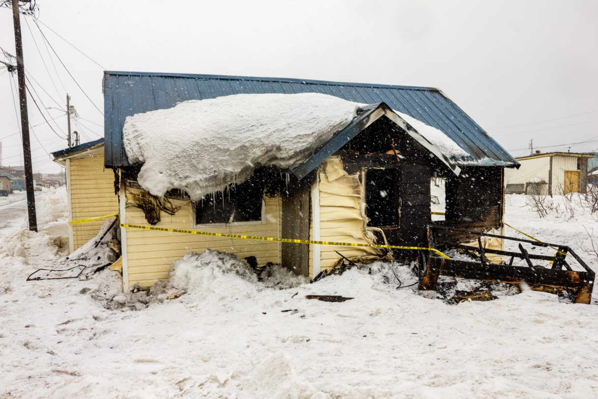 A house heavily damaged by fire, seen on a snowy afternoon in a rural Alaska town.