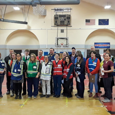 Group of people wearing colorful, reflective vests stand together inside a large gymnasium.