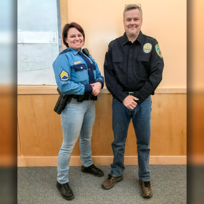 Two law enforcement officers in Nome stand smiling, wearing denim jeans.