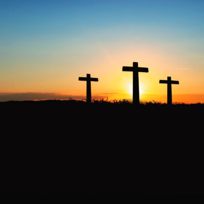 Silhouette of three crosses on a hillside set against a setting sun.