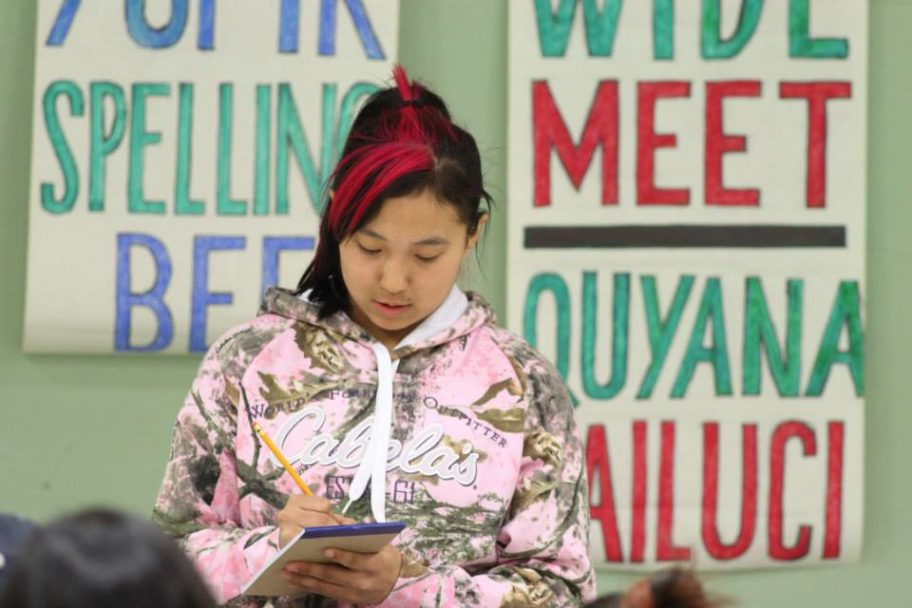 "a young girl writes on a notepad with a pencil, with posters behind her that read ""Spelling Bee"" and ""Quyana"""