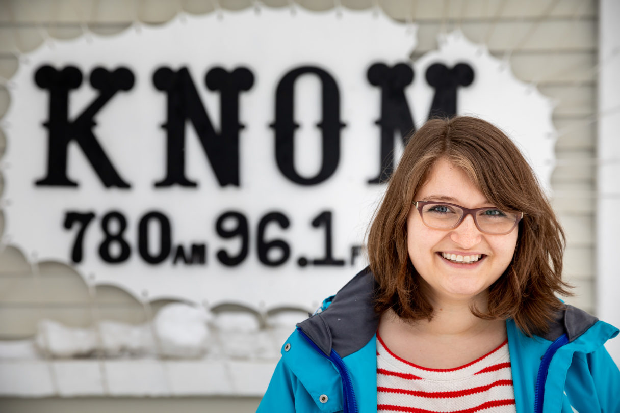 """Woman in blue jacket and red-and-white shirt stands in front of sign that reads """"KNOM 
