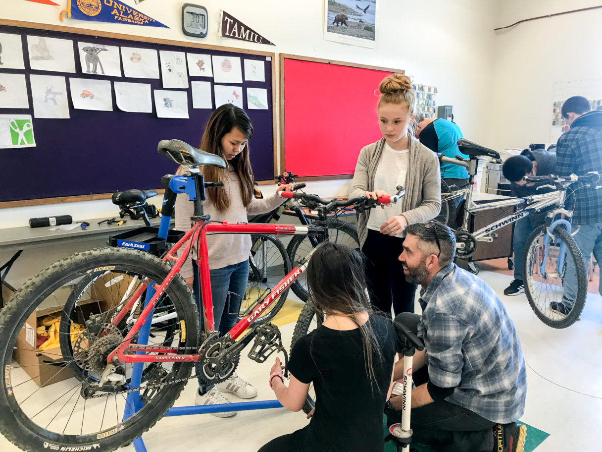 High school students stand around a bicycle during a repair session in a classroom.