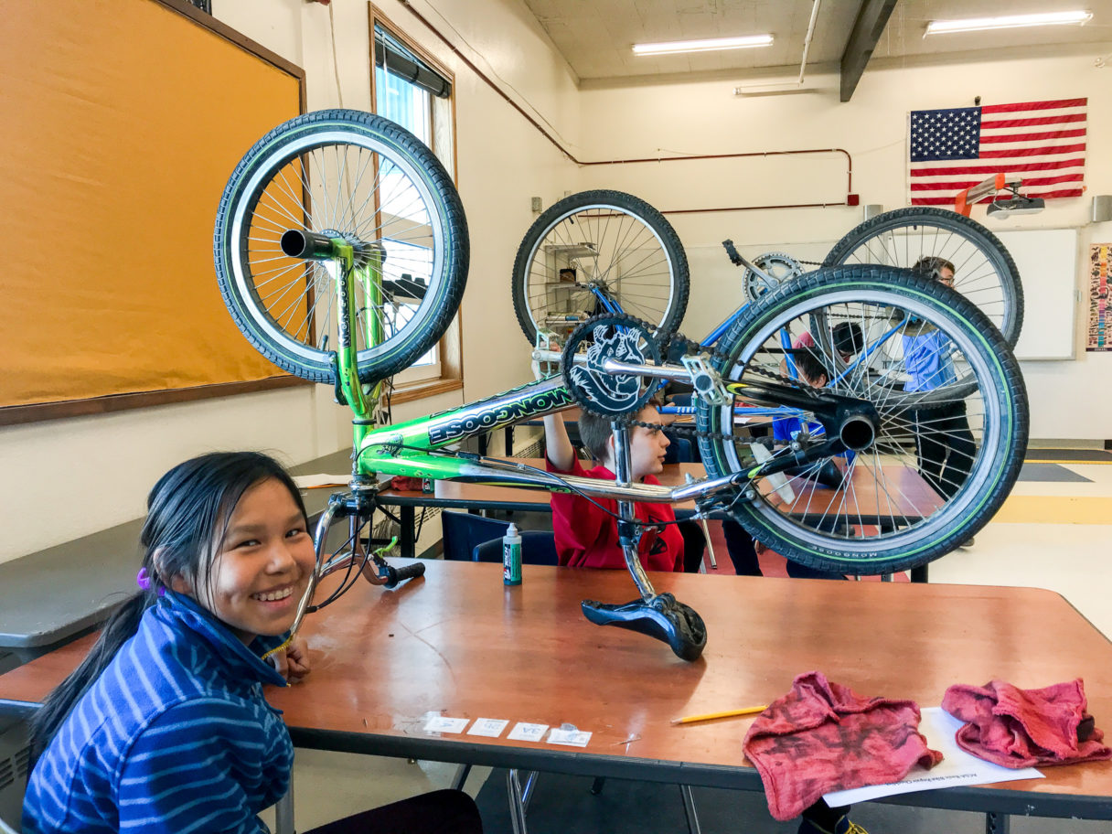 A student smiles at the camera, seated at a table on which stands a bicycle being repaired.