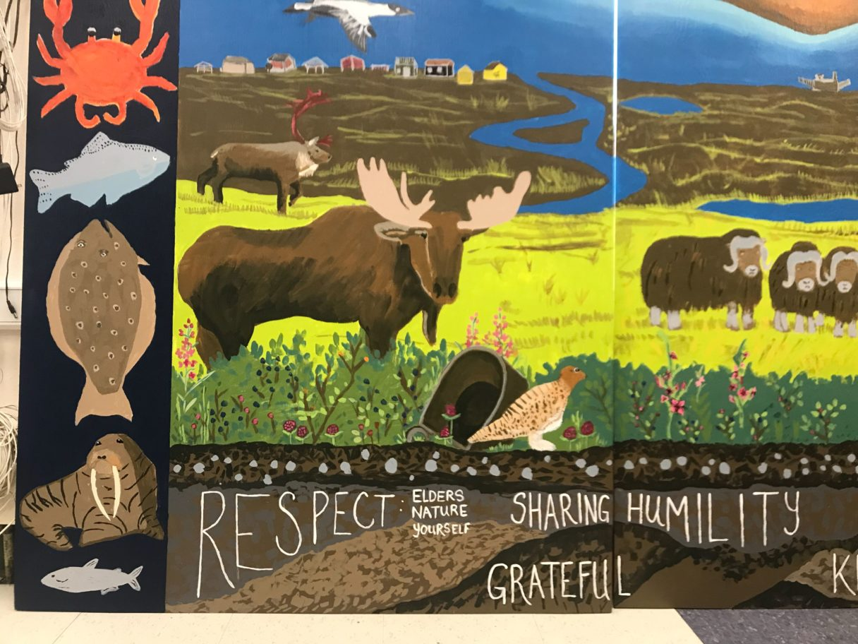 "Close-up detail of a large mural, depicting moose, muskoxen, and words saying ""Respect Elders, Nature, and Yourself; Grateful; Sharing; Humility."""