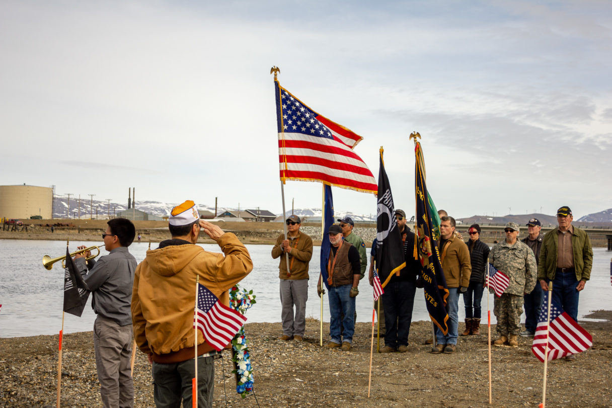 """Veteran salutes flag and color guard while bugler plays """"Taps."""""""