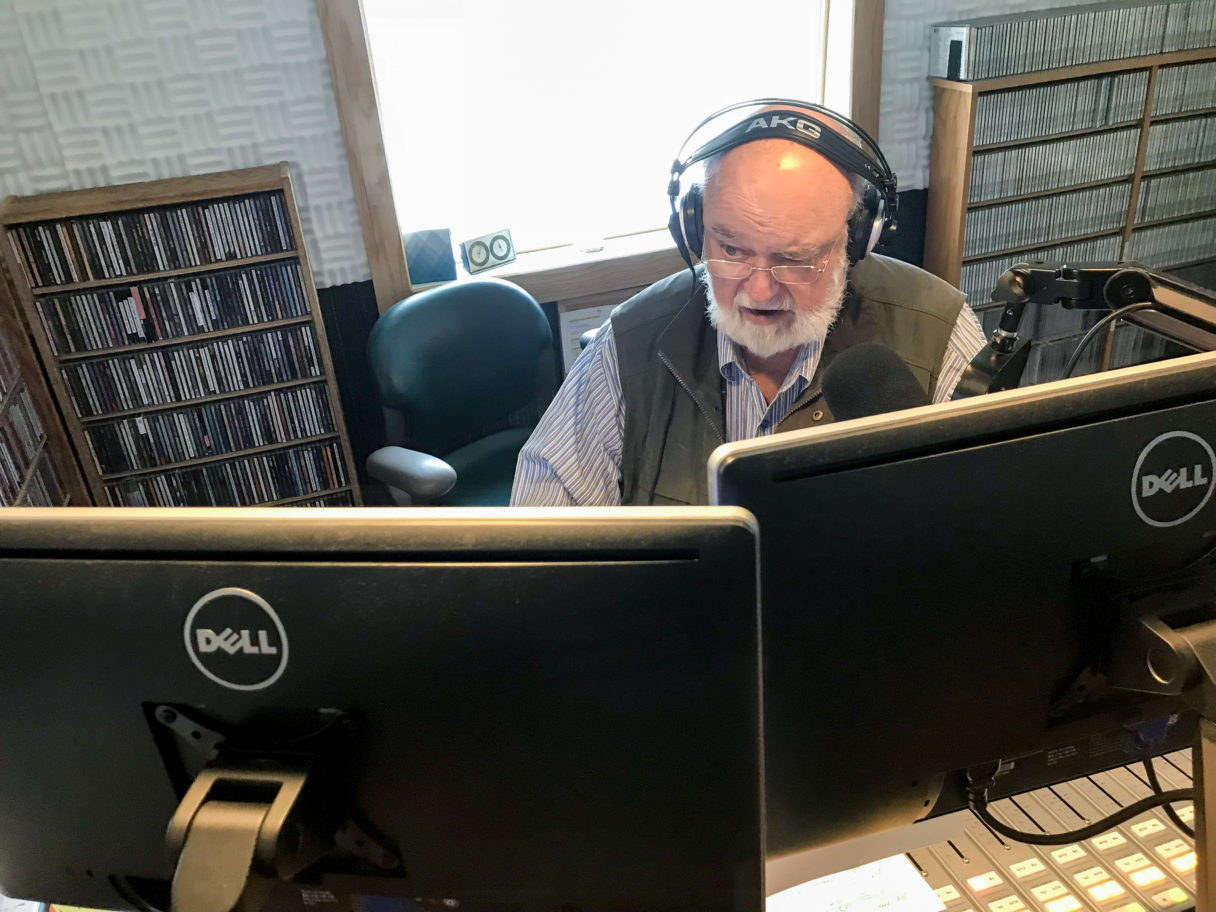 Man with white beard and headphones sits in front of computer screens and radio microphone