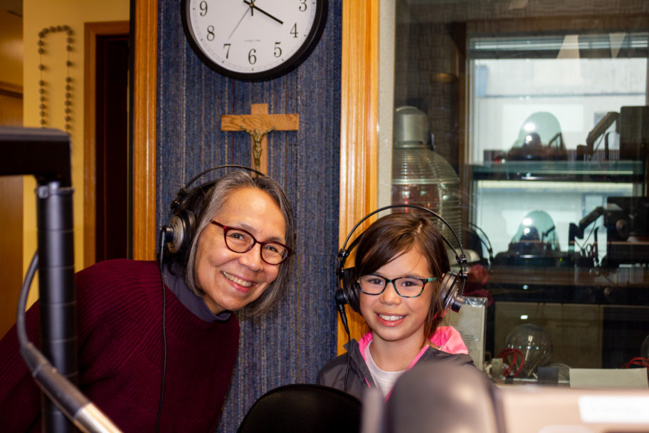 Middle-aged woman and young child smile from behind radio microphone inside studio