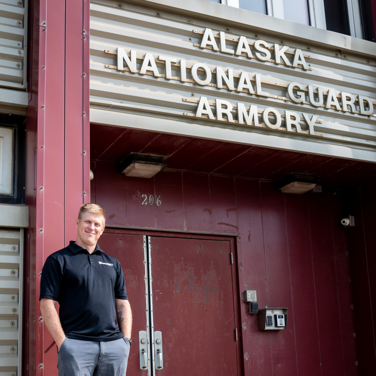 Man in black polo shirt stands outside the Alaska National Guard Armory in Nome