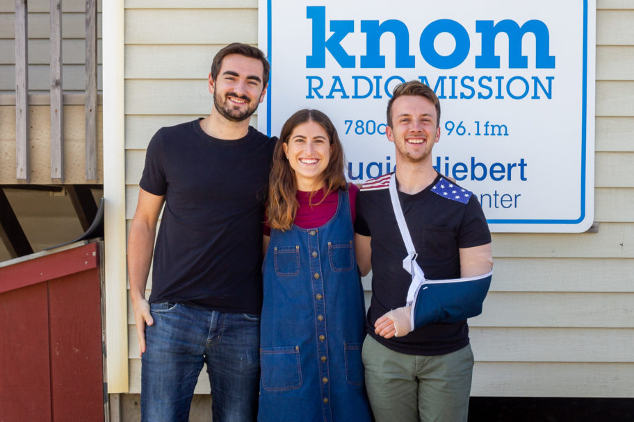 "Three young people stand smiling in front of a sign that reads ""KNOM Radio Mission."""