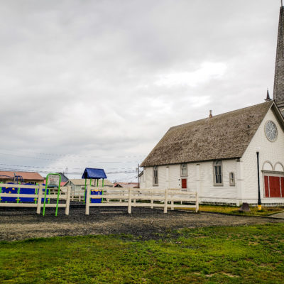 A children's playground area next to a grassy field and a white clapboard church