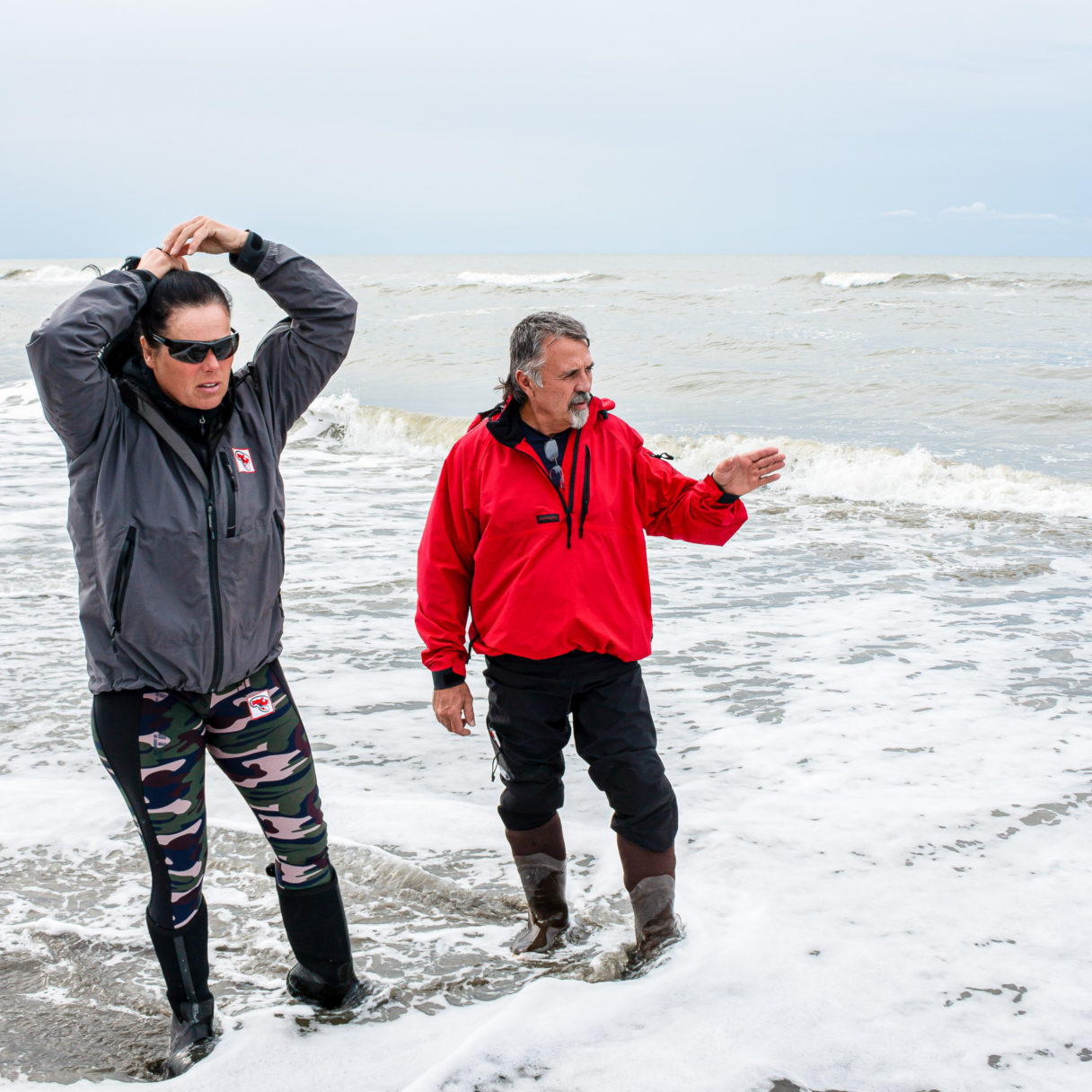 Two people look at the ocean waves of the Bering Sea, standing in knee boots in the low surf.