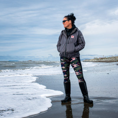 Woman in technical clothes stands on rural Alaska beach on a cloudy day