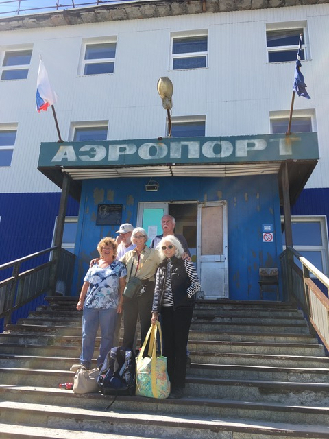 "A group of travelers stands in front of a building with the word ""airport"" written in Russian: ""AЭРОПОРТ."""