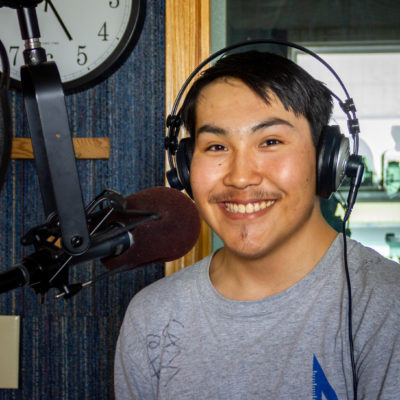 Young man in grey t-shirt smiles while standing behind a radio microphone