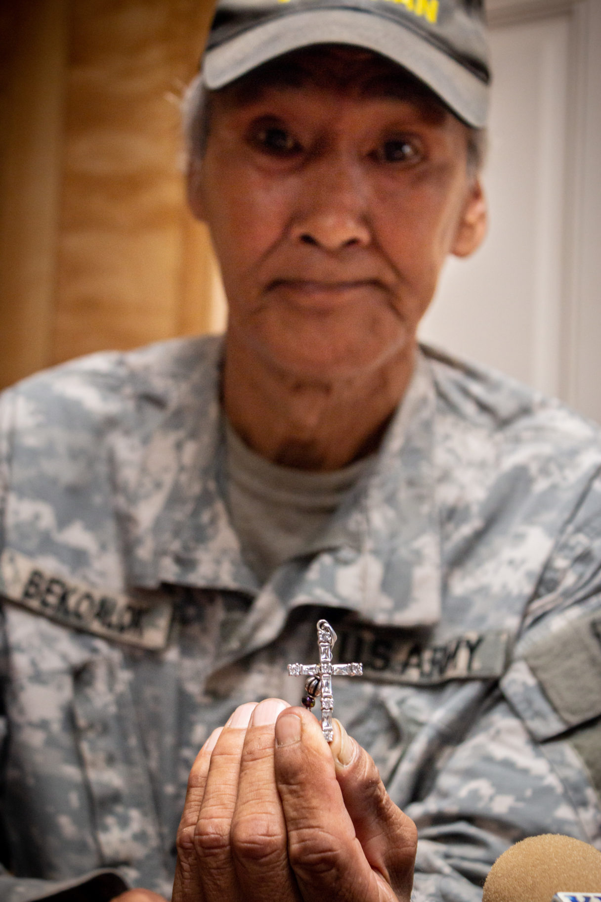 Man in Army uniform holds small silver cross