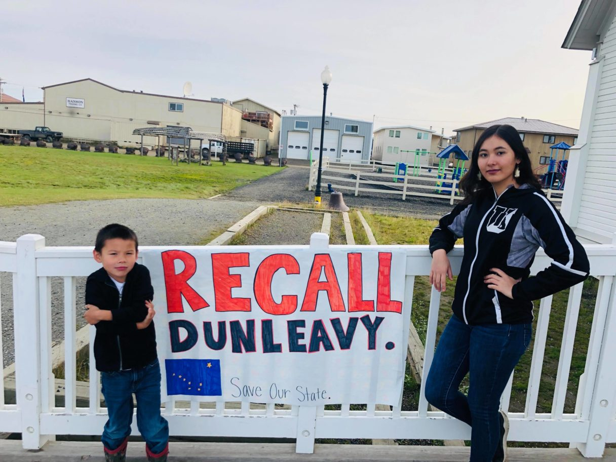 """A woman and a young child stand next to a sign reading """"Recall Dunleavy"""""""