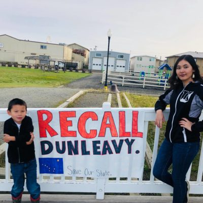 "A woman and a young child stand next to a sign reading ""Recall Dunleavy"""