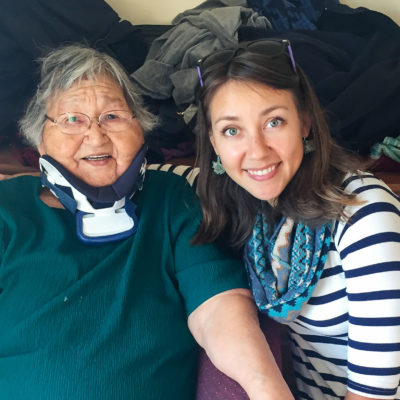 Elderly woman and young woman sit smiling, side-by-side