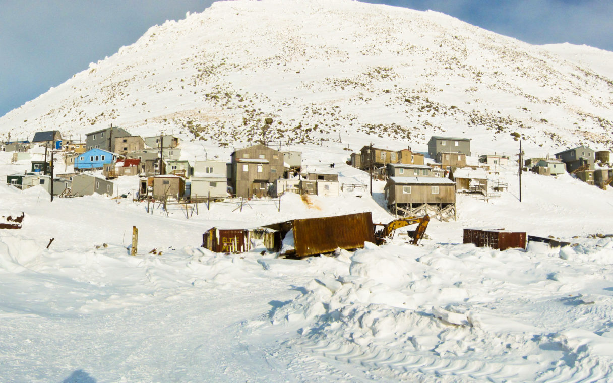 A photo of homes and buildings in Diomede, a small community on an island in the Bering Sea.