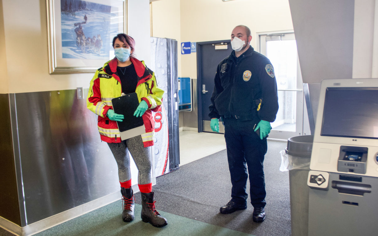 A female EMT and a male police officer wear masks and gloves in the terminal of the Nome airport.